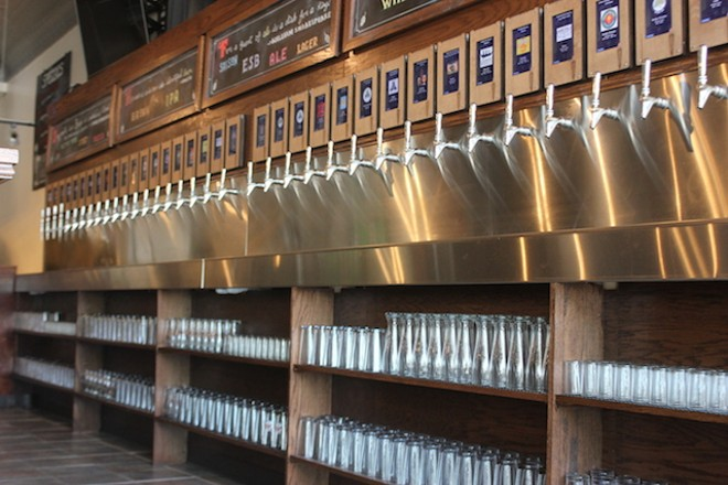 Glasses are stored under the row of taps for easy access. - PHOTO BY SARAH FENSKE
