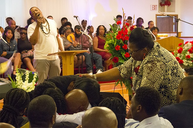 """The family of Edward Crawford embraces during a rendition of """"My soul has been anchored in the Lord."""" - PHOTO BY DANNY WICENTOWSKI"""
