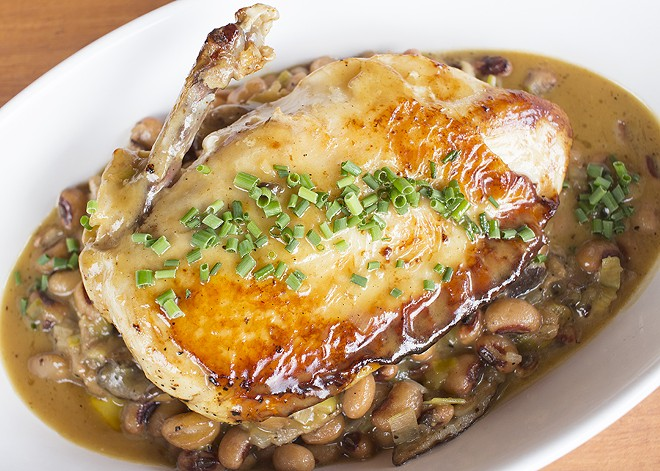 A cast iron-seared chicken breast is served over shiitake mushroom and leek-braised beans with lemon-garlic pan jus. - PHOTO BY MABEL SUEN