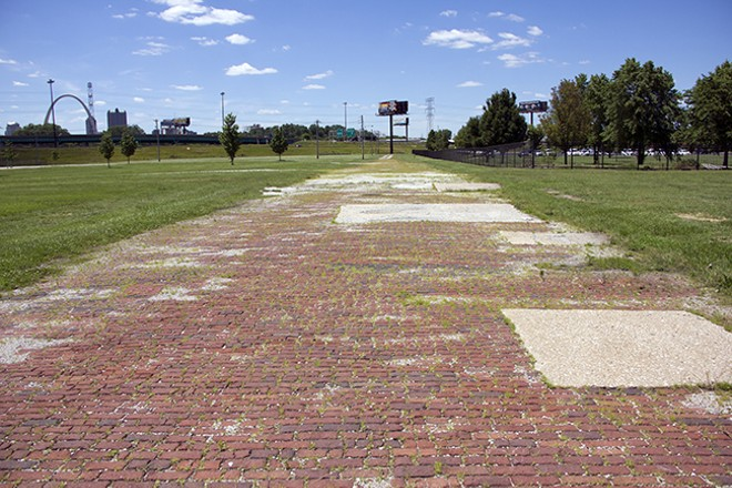 The remains of a century-old brick road runs partway through a grass field in East St. Louis. - PHOTO BY DANNY WICENTOWSKI