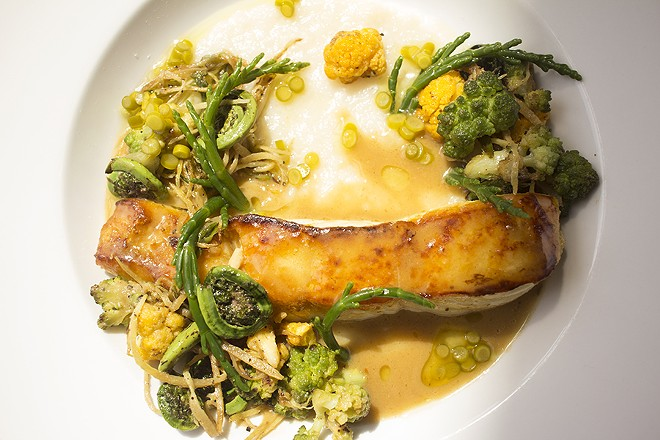 Lacquered halibut is served with miso butter, jasmine congee, fiddle heads, confit garlic scapes, sea beans, cauliflower and broccoli. - MABEL SUEN