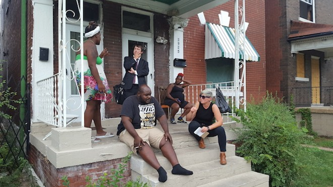 Je're Reid, far left, talks to Lee Camp of ArchCity Defenders. - PHOTO BY ROBERT LANGELLIER