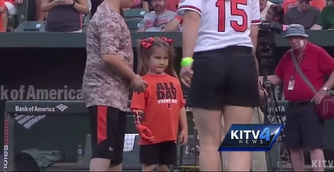 Hailey Dawson, shown here with her 3D-printed hand before throwing an opening pitch at an Orioles game. - VIA KITV/YOUTUBE