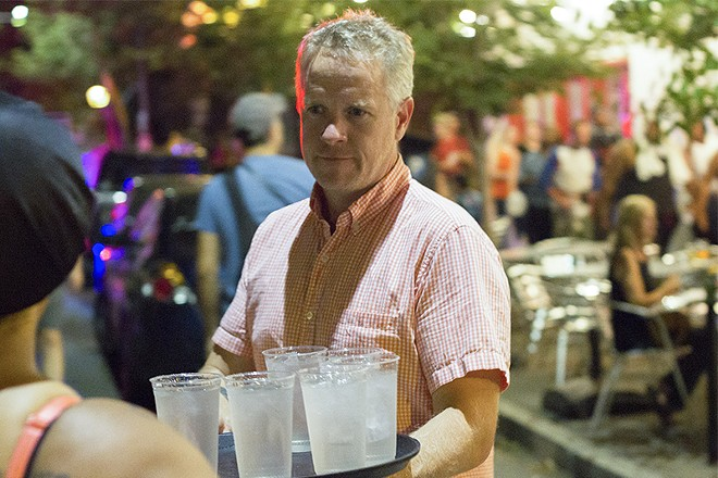 Pi Pizzeria owner Chris Sommers distributing cups of water to protesters Friday night. - PHOTO BY DANNY WICENTOWSKI