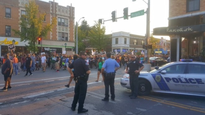 A pair of Olivette cops watch the protest go by. - PHOTO BY DANNY WICENTOWSKI