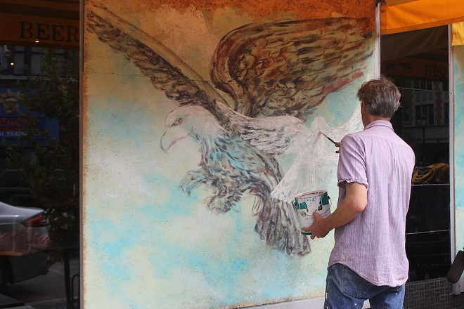 An artist paints the plywood covering Salt + Smoke with an illustration showing an eagle — and a dove. - PHOTO BY SARAH FENSKE