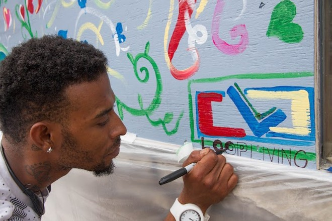 Jomar Jackson paints at Loop Living. - COURTESY OF PAINTING FOR PEACE IN FERGUSON, A CHILDREN'S BOOK