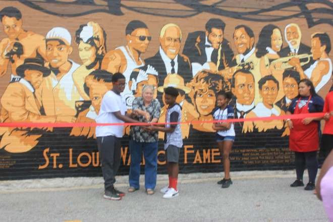 St. Louis artist Grace McCammond and Boys and Girls Club artists cut the ribbon at the presentation of the new St. Louis Wall of Fame. - PHOTO BY ELIZABETH SEMKO.