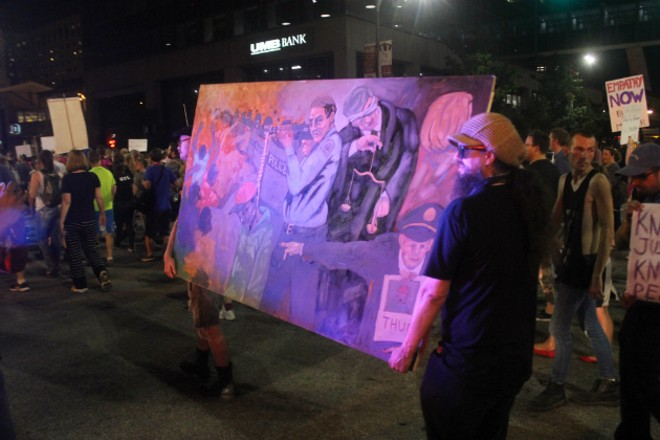 Protesters carried a painting inspired by the Jason Stockley case. - PHOTO BY DOYLE MURPHY