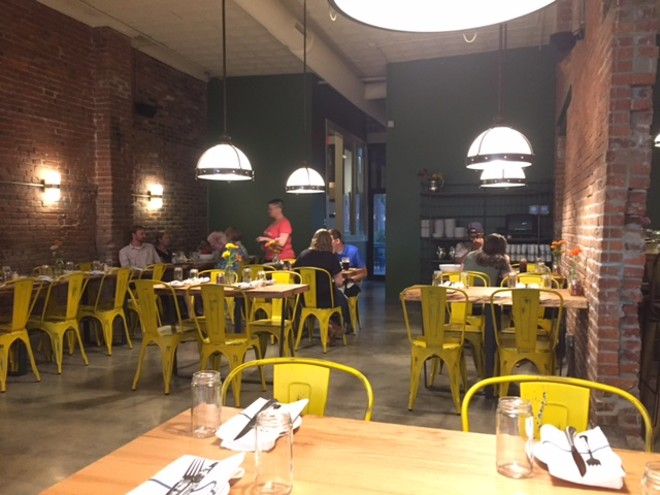 Brick walls line the restaurant, with yellow chairs for a splash of color. - PHOTO BY SARAH FENSKE