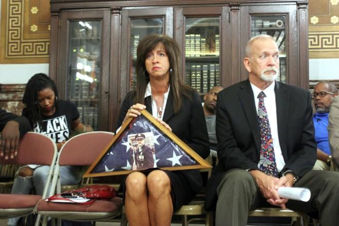 Kimberly Kowalski holds a photo of her husband, Sgt. Jeffrey Kowalski, who shot in 1987. - PHOTO BY DOYLE MURPHY