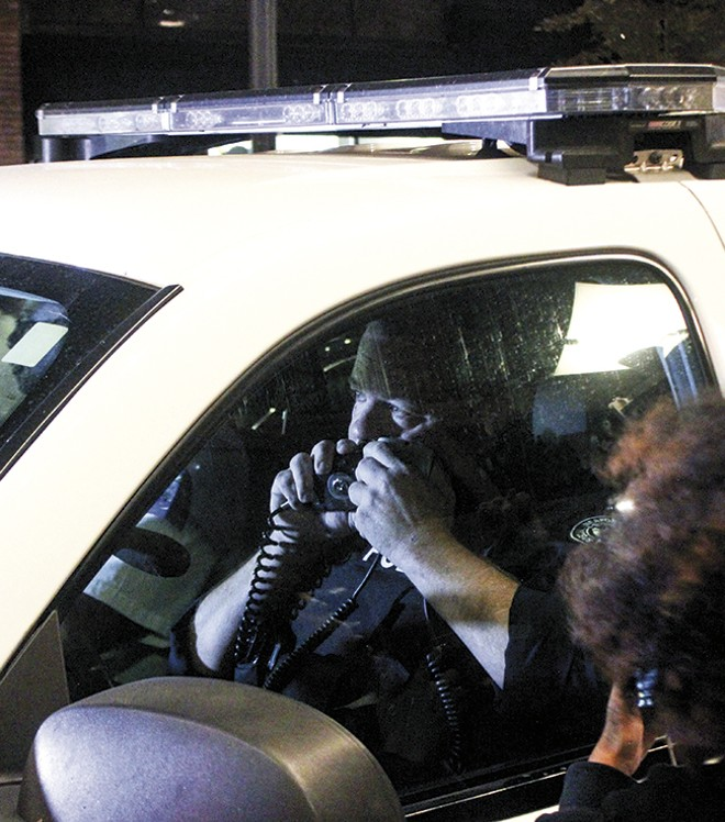 Sgt. Brian Rossomanno speaks into his radio as protesters 'kettle' him on Sept. 28 in downtown St. Louis. - DOYLE MURPHY