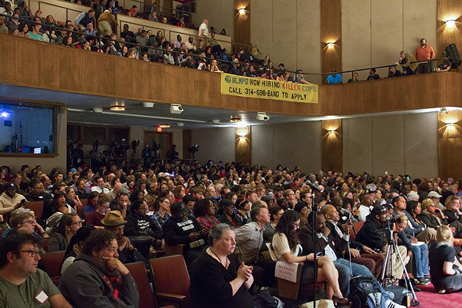 """During the town hall, audience members unfurled a banner reading """"SLMPD Now Hiring Killer Cops."""" - DANNY WICENTOWSKI"""