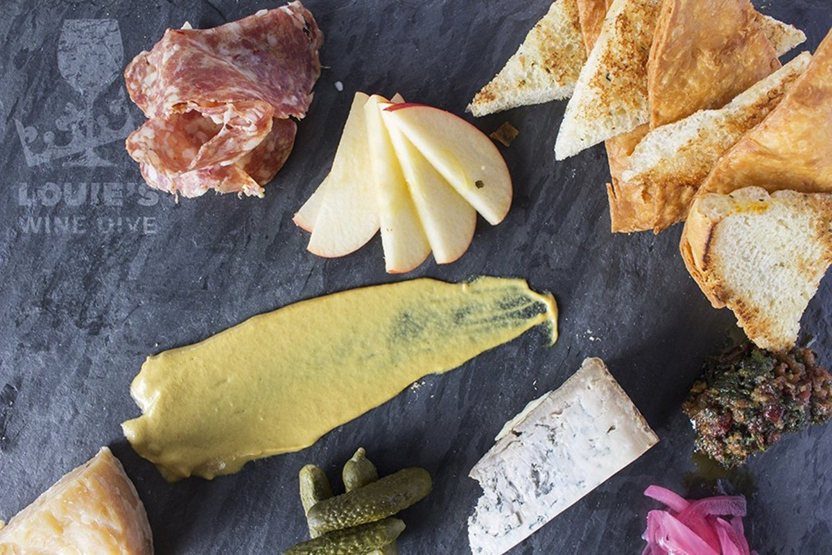Louie's personalizable charcuterie board features a variety of meat and cheese served with foccacia, crackers, cornichon relish, bacon jam, apples, pickled onions and mustard.