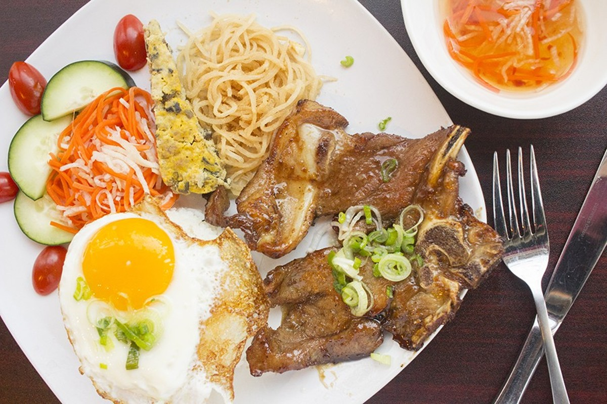 Com Tam Dac Biet includes a grilled honey-glazed lemongrass pork chop, a fried egg, a Vietnamese egg cake and shredded pork skin with broken rice.