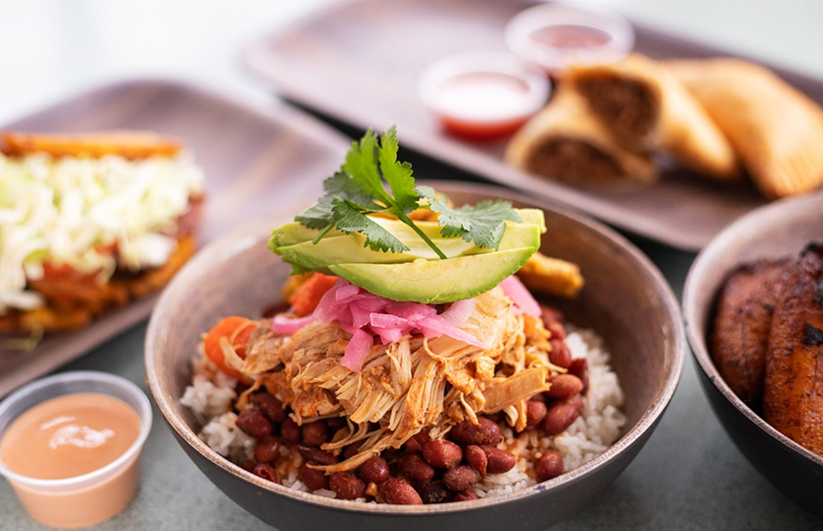 Pollo Guisado with braised chicken, vegetables, red beans, white rice, tostones, pickled onion and avocado.