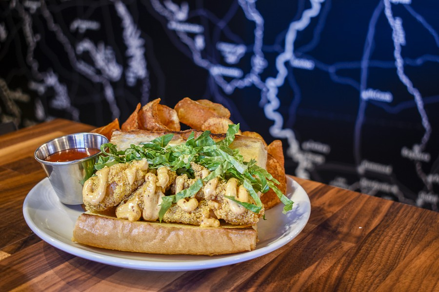 The shrimp po'boy is topped with remoulade and shredded romaine. - KELLY GLUECK