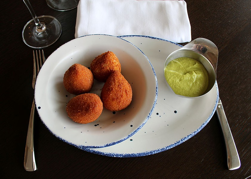 The coxinha, fried balls of chicken and Brazilian cream cheese, served with aji amarillo sauce. Craft referred to these as chicken nuggets as a child. - LEXIE MILLER