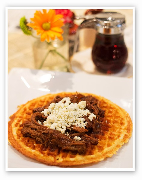 "A ""Blue Ox"" cornmeal waffle with caramelized onions, slow cooked brisket,       bourbon lime sauce and blue cheese. 
