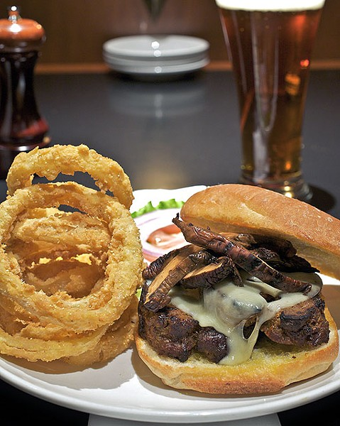 The grilled meatloaf sandwich is served with wild mushrooms, Swiss cheese and chipotle ranch dressing on a ciabatta roll. It is shown here with onion rings. See more photos from inside Hanley's in this slideshow. - PHOTO: JENNIFER SILVERBERG