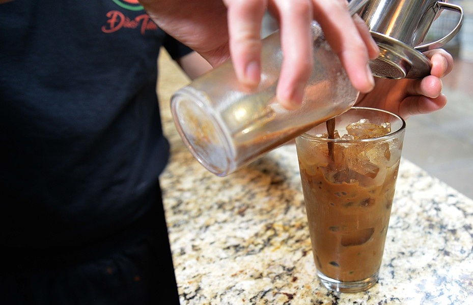 Sunny Dinh pours Dao Tien's coffee over ice after it is finished descending through a French press. - TOM HELLAUER