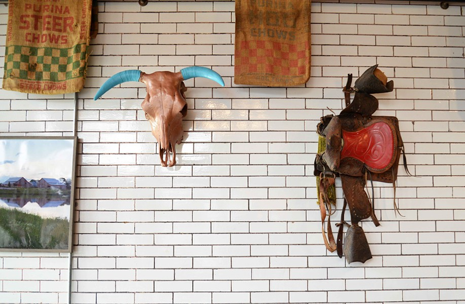 Schulze's former pet cow's skull and saddle now adorn the walls of Red Oak Biscuits. - TOM HELLAUER