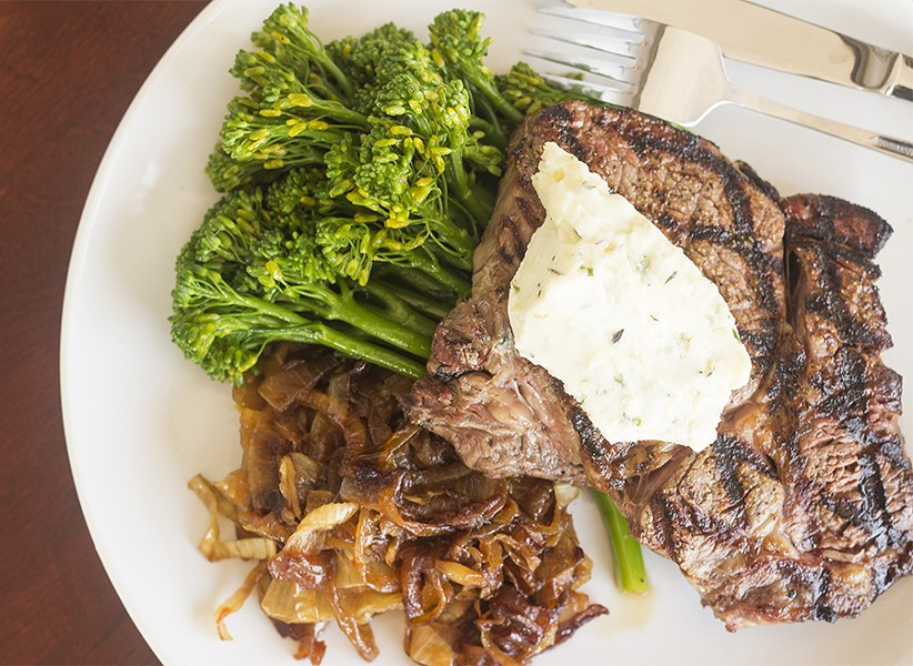 The hand-cut beef ribeye features a twelve-ounce portion served with bleu-cheese butter, whiskey onions and a vegetable side. - MABEL SUEN
