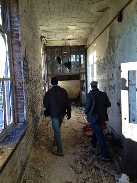 Nathan Dell (left) and Nelson Perez search an abandoned school in north St. Louis. - PHOTO BY DOYLE MURPHY