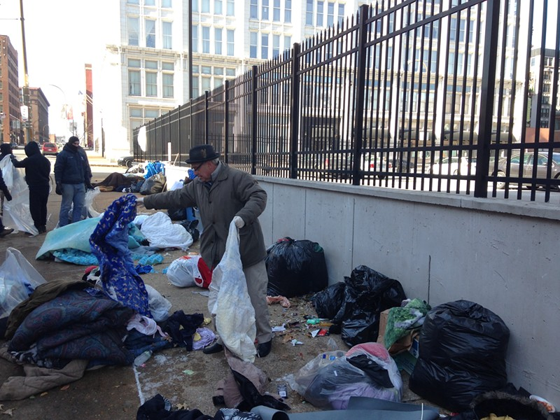 St. Louis Director of Human Services Eddie Roth on Wednesday sorts through a homeless encampment on Locust Street. - PHOTO BY DOYLE MURPHY