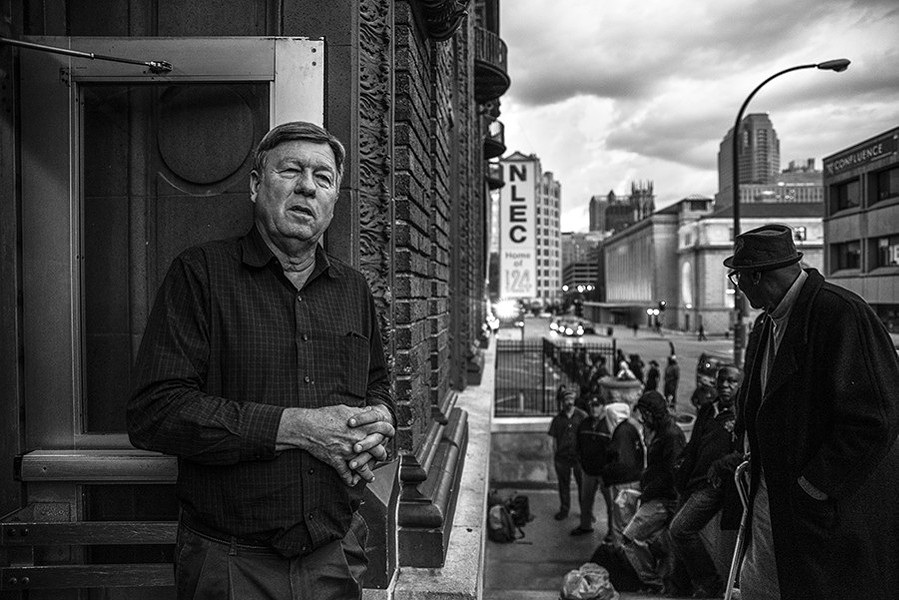 Rev. Larry Rice looks out the front door of the New Life Evangelistic Center as homeless men wait in line for potential beds for the night on November 14. - PHOTO BY NICK SCHNELLE