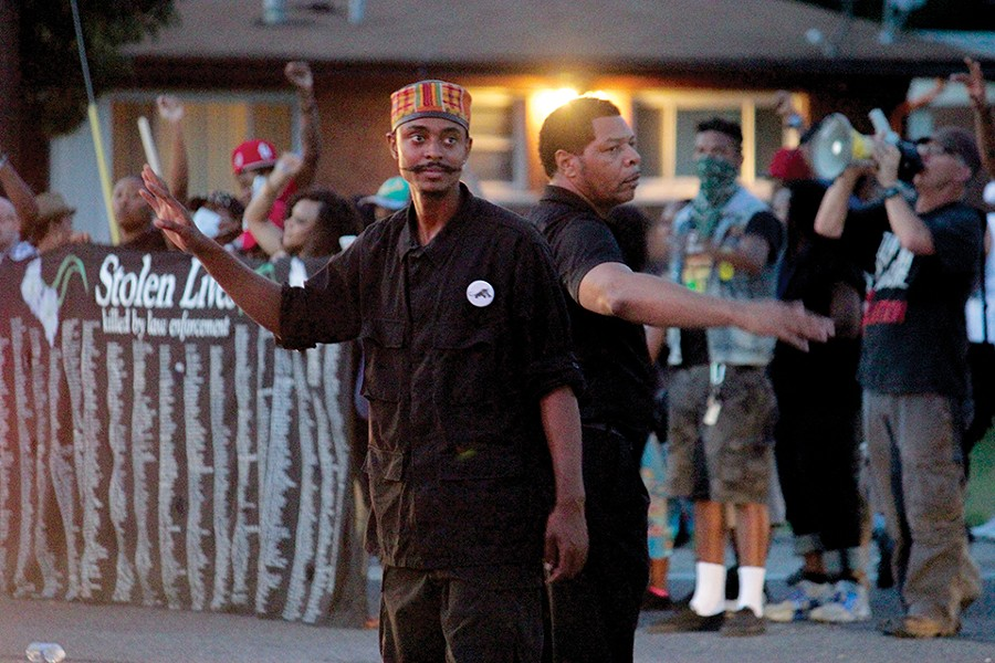 In Ferguson, Davis and other New Black Panthers joined protesters just hours after Michael Brown's death. In this image from August 14, 2014, Davis helps direct traffic during a demonstration. - DANNY WICENTOWSKI