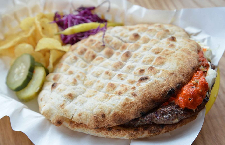 "The pljeskavica or ""balkan burger"" is grilled and placed on a flatbread with cheese, kajmak and somun. - TOM HELLAUER"