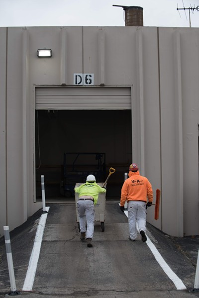 Workers roll a cart up a loading dock where bodies would enter the morgue. - TRENTON ALMGREN-DAVIS