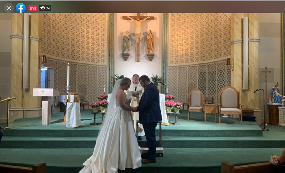 Katie and Zach Hawkins bow their heads in prayer as their priest marries them. The two hosted a Facebook live stream to celebrate their wedding during COVID-19. - SCREENGRAB FROM THE LIVE STREAM OF KATIE AND ZACH HAWKINS' WEDDING.