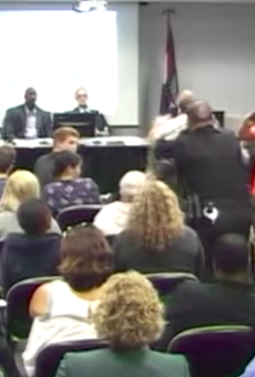 A man with a camera reacts as a St. Louis police officer knocks down Steve Taylor, an instructor attempting to speak at October 19's board of trustee meeting.