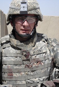 Ethan McCord on a rooftop in Baghdad on July 12, 2007, shortly after he rescued two wounded children from a van that was fired upon by U.S. Army helicopters. Blood from the children can be seen on his uniform.