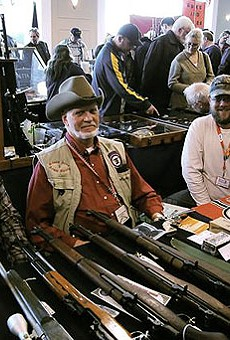 Alan Fasoldt (center) and father-son team Dominic Sr. (Left) and Dominic Jr. (Right) smile behind their collection of M1 Garands, ammo and war memorabilia.