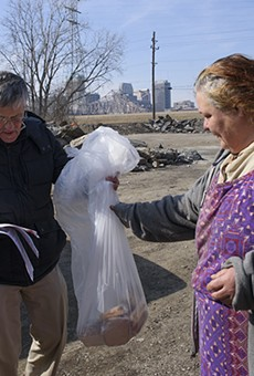 Ray Redlich (in black) and Chris Ohnimus, pictured here giving sandwiches to a resident of a homeless camp, were ticketed for distributing sandwiches in St. Louis.