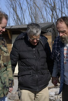From left, Chris Ohnimus and Ray Redlich pray with Robert Gibson at homeless encampment in 2018 in East St. Louis.