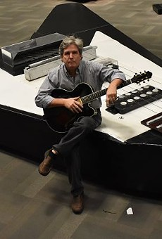 HP Newquist, executive director of the National Guitar Museum, sits atop the world's largest guitar.