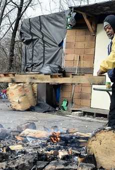 Robert Gibson (left) and Orlando Giles lift a pallet onto a fire at the East St. Louis camp.