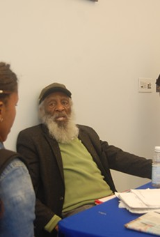 Scholars Brittany R. Mosley and Jeremy Shaw gathered around Dick Gregory to have autographs signed and ask questions.