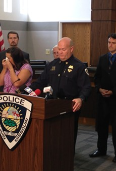 Sara Flamion (left) wipes away tears as Ballwin police Chief Kevin Scott describe's wounds suffered by her husband, Officer Mike Flamion.