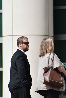 Ex-Mississippi County Sheriff Cory Hutcheson walks into federal court with his wife, Brittney.