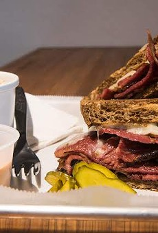 The pastrami sandwich with a side of potato salad.