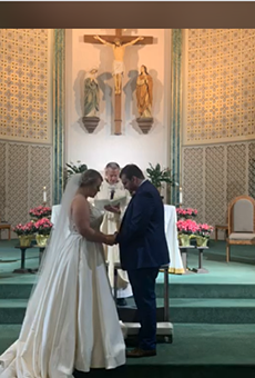 Katie and Zach Hawkins bow their heads in prayer as their priest marries them. The two hosted a Facebook live stream to celebrate their wedding during COVID-19.
