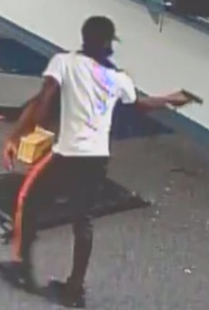 """""""Subject 6"""" shown with a gun inside Lee's Pawn and Jewelry."""