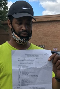 Terrell Porter is holding the letter his wife Janica Washington received from Sansone Group, the owner of Southwest Crossing apartments. The letter informed the couple they had violated tenant rules because of what she said in an RFT story published in August.