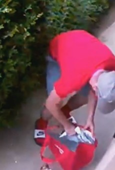 Security footage shows a porch pirate as he puts a white Amazon package into a DoorDash bag.