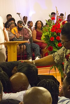 """The family of Edward Crawford embraces during a rendition of """"My soul has been anchored in the Lord."""""""
